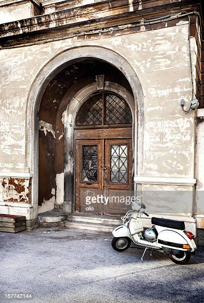 Rollstuhl vor einer verwitterten Tür