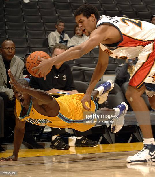 Scooter McFadgon of the New Orleans/Oklahoma City Hornets dives for the ball against Patrick O'Bryant of the Golden State Warriors during a preseason...