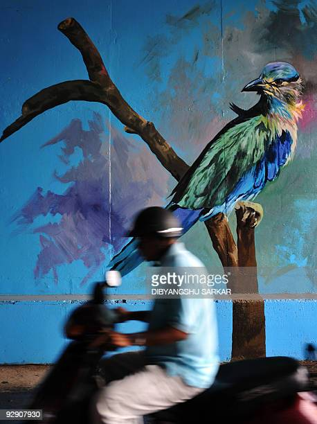A scooterist drives past a painting on the side wall of an underpass road in Bangalore on November 9 2009 Bruhat Bangalore Mahanagara Palike Greater...