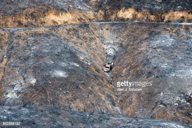 A scorched hillside and car is revealed after the La Tuna Canyon fire moved through the hills near Crestline Drive in Los Angeles Sunday Sept 3 2017...