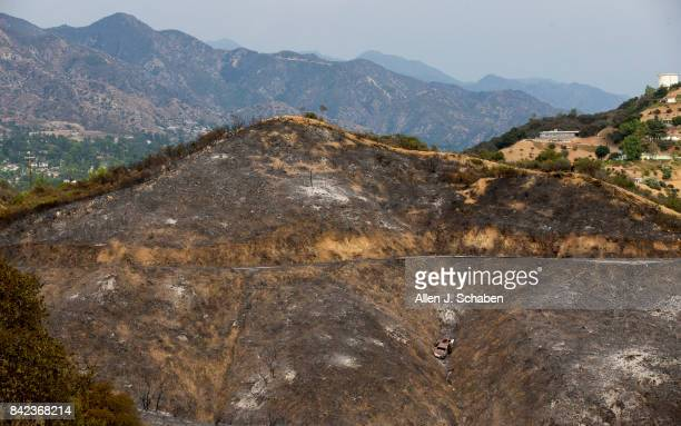 A scorched hillside and car is revealed after the La Tuna Canyon fire moved through near Crestline Drive in Los Angeles Sunday Sept 3 2017...