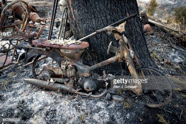 A scorched motorcycle at a home lies in ruin as it was one of three homes and a shed were destroyed in the the La Tuna Canyon fire along Crestline...