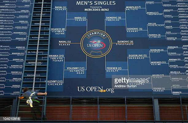 A score keeper adds Novak Djokovic's name to the draw board after Djokovic's win over Roger Federer of Switzerland during the men's singles semifinal...