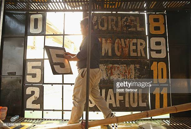 A scoreboard attendant adjusts the score from inside of the scoreboard during the ICC World Twenty20 Bangladesh 2014 match between Pakistan and...