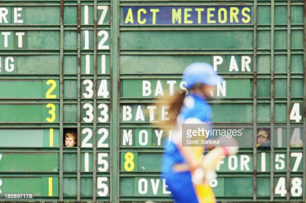 Scoreboard attendants look out from inside the scoreboard during the WNCL match between Victoria and the ACT at Russell Lucas Oval on October 26 2013...