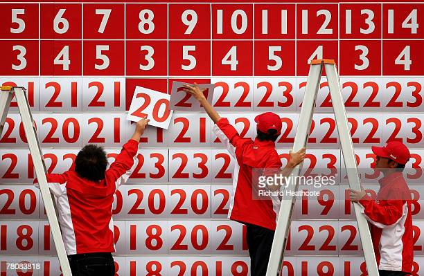 Scoreboard staff put up numbers during the final round of the Omega Mission Hills World Cup at the Mission Hills Resort on 25 November 2007 in...
