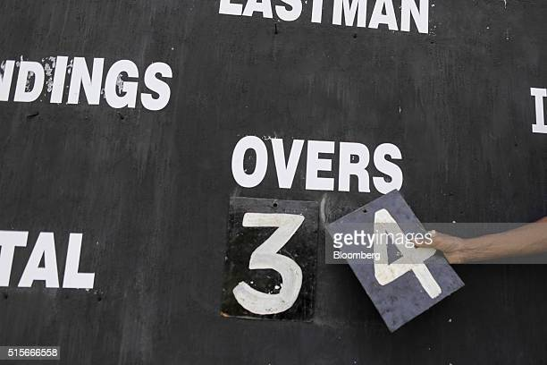 A scorekeeper changes a numbercard on a scoreboard to indicate the number of overs bowled during a cricket match at the Bombay Gymkhana in Mumbai...