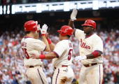 Scoring runners Cole Hamels and Carlos Ruiz celebrate with teammate Ryan Howard of the Philadelphia Phillies after a Chase Utley double in the third...