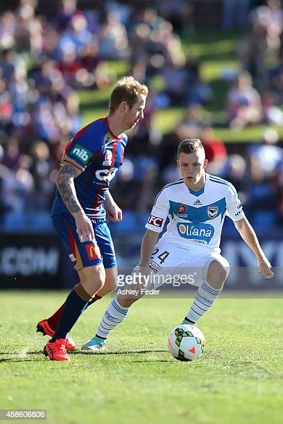 Scot Galloway of the Victory controls the ball ahead of David Carney of the Jets during the round five ALeague match between Newcastle Jets and...