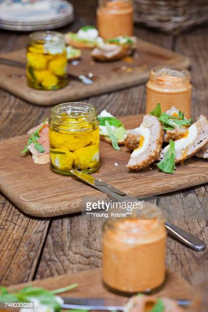 Scotch eggs on wooden chopping boards with sauce
