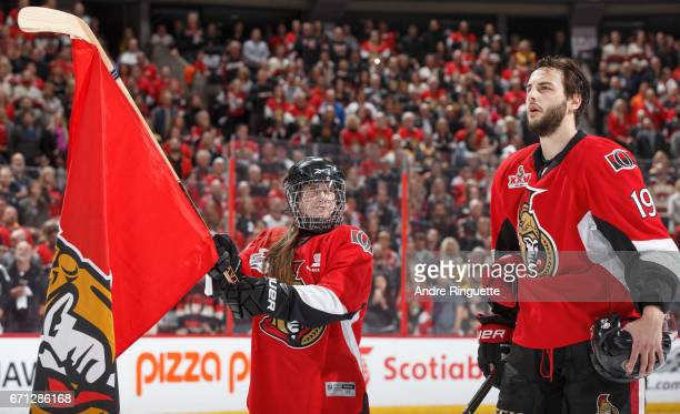 Scotiabank skater looks up at Derick Brassard of the Ottawa Senators during the singing of the national anthems prior to a game against the Boston...