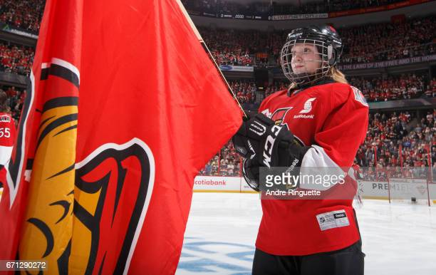 Scotiabank Skater stands at attention holding a team flag during the singing of the national anthems prior to a game between the Ottawa Senators and...