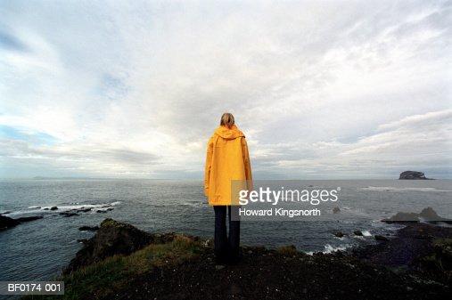 Scotland, Aberlady Bay, woman wearing waterproof coat, rear view
