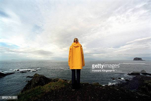 Scotland, Aberlady Bay, woman wearing waterproof coat, rear view