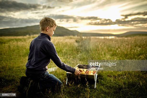 UK, Scotland, boy grilling in rural landscape