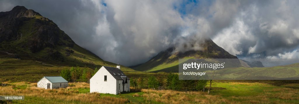 Scotland crofters cottage in dramatic Highland mountain glen pan