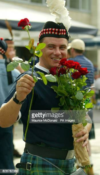 A Scotland fan hans out roses to passersby in the City centre of Dortmund before tomorrow's Euro 2004 Qualifier against Germany