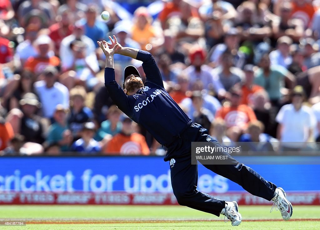 Scotland fieldsman Kyle Coetzer dives to take a catch to dismiss England batsman Eoin Morgan during their 2015 Cricket World Cup Group A match in...