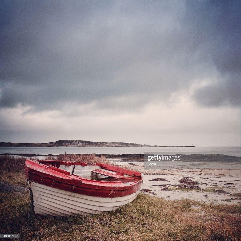 UK, Scotland, Inner Hebrides, Jura, Red and white boat on grass