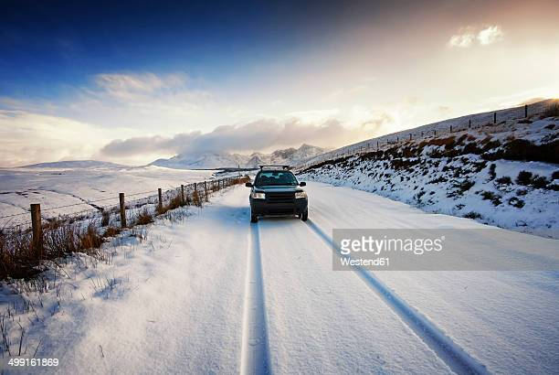 UK, Scotland, Isle of Skye, Cuillin Mountains, four wheel drive vehicle driving on snow-covered street