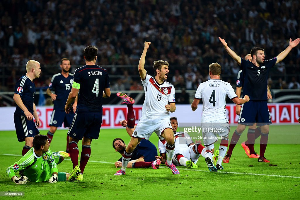 Scotland players react as Thomas Mueller of Germany (13) celebrates scoring their second goal during the EURO 2016 Group D qualifying match between Germany and Scotland at Signal Iduna Park on September 7, 2014 in Dortmund, Germany.