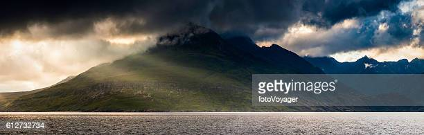 Scotland rays of sunlight stormclouds over Cuillin mountains panorama Skye