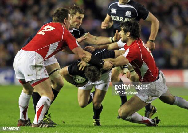 Scotland scrum half Rory Lawson is tackled by Wales' hooker Matthew Rees and scrum half Mike Phillips during the Six Nations International rugby...