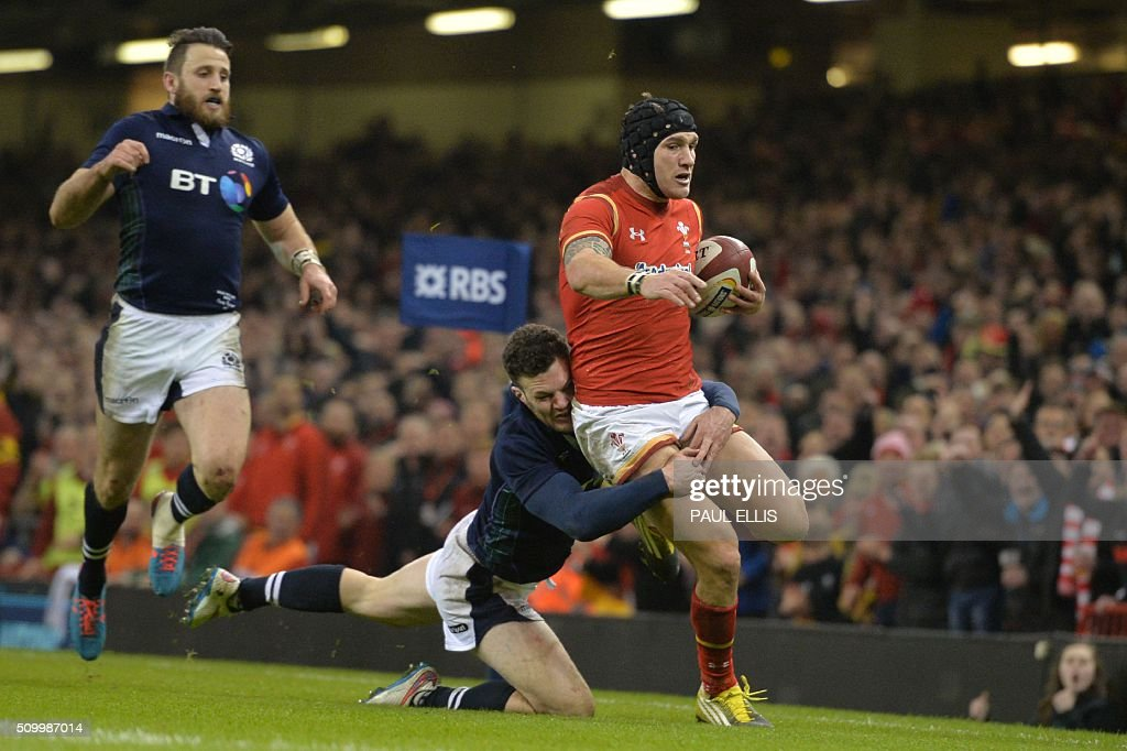 Scotland's centre Duncan Taylor (2L) tackles Wales' wing Tom James (R) just before the try line during the Six Nations international rugby union match between Wales and Scotland at the Principality Stadium in Cardiff, south Wales, on February 13, 2016. / AFP / PAUL ELLIS / RESTRICTED TO EDITORIAL USE. Use in books subject to Welsh Rugby Union (WRU) approval.