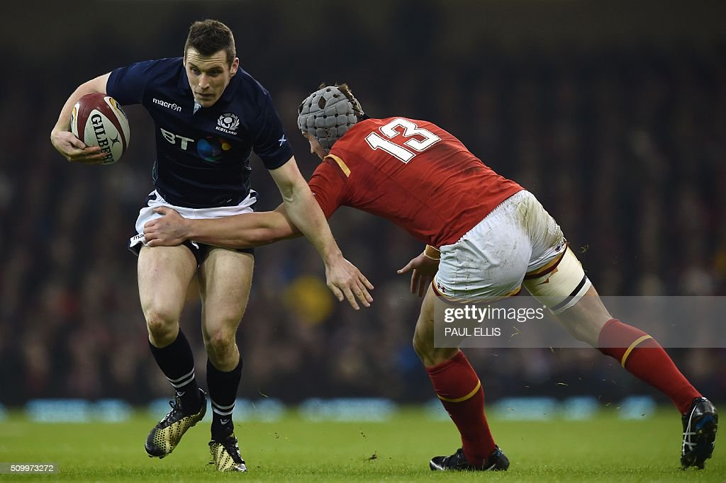 Scotland's centre Mark Bennett is tacked by Wales' centre Jonathan Davies during the Six Nations international rugby union match between Wales and Scotland at the Principality Stadium in Cardiff, south Wales, on February 13, 2016. / AFP / PAUL ELLIS / RESTRICTED TO EDITORIAL USE. Use in books subject to Welsh Rugby Union (WRU) approval.
