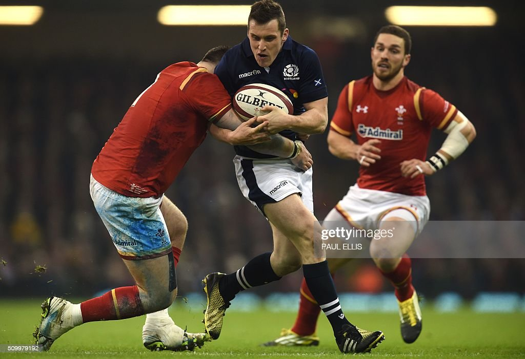 Scotland's centre Mark Bennett (C) is tackled during the Six Nations international rugby union match between Wales and Scotland at the Principality Stadium in Cardiff, south Wales, on February 13, 2016. / AFP / PAUL ELLIS / RESTRICTED TO EDITORIAL USE. Use in books subject to Welsh Rugby Union (WRU) approval.