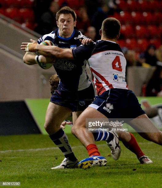 Scotland's David Scott is tackled by USA's Michael Garvey and Matthew Petersenduring the the 2013 World Cup match at Salford City Stadium Salford