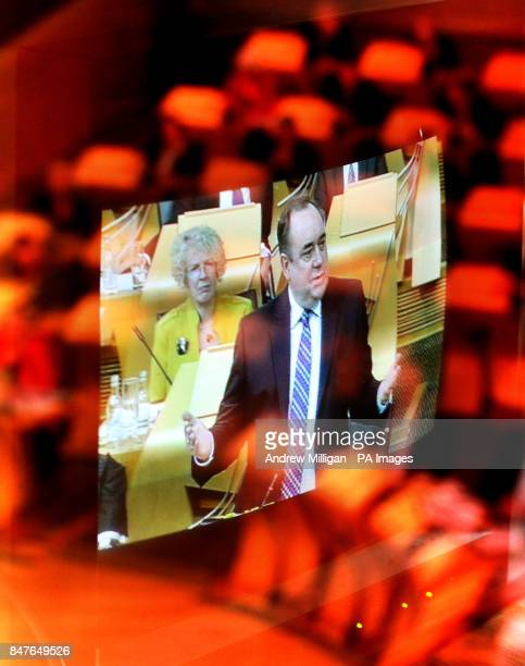 Scotland's First Minister Alex Salmond is photographed on a television screen in a translation booth with the chamber reflected on the window during...