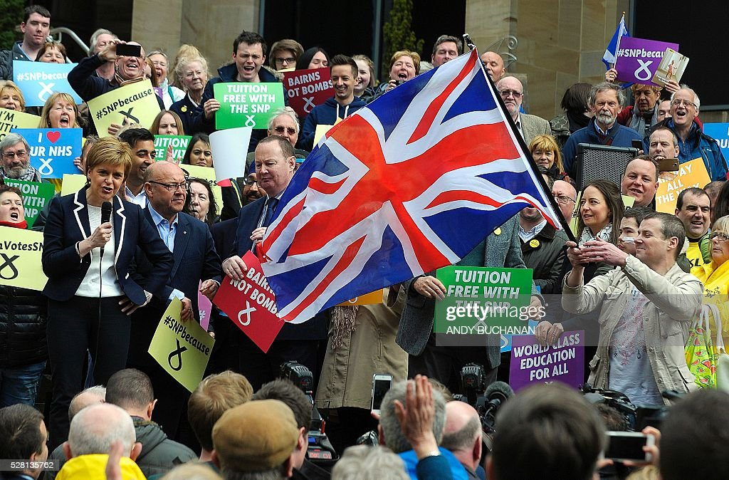 Scotland's First Minister and Leader of the Scottish National Party (SNP), Nicola Sturgeon (L), reacts as she is interrupted by a man waving a Union flag as she speaks during a campaign event in Glasgow, on May 4, 2016, on the eve of regional elections. The Scottish National Party heads into regional elections on May 5, hoping to strengthen its clout and secure a mandate to demand independence if Britain leaves the European Union. Wales and Northern Ireland will also elect new national assemblies, with elections also taking place in 124 English local authorities on the same day. / AFP / Andy Buchanan