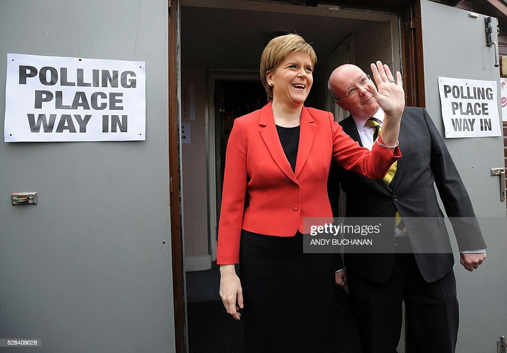 Scotland's First Minister and Leader of the Scottish National Party (SNP), Nicola Sturgeon (L), and her husband Peter Murrell, pose for photographers as they leave a Polling Station at Broomhouse Community Hall in east Glasgow, on May 5, 2016, after casting their votes. While London chooses a new mayor, there are also elections to the Scottish, Welsh and Northern Irish assemblies, and 124 local authorities scattered across England. / AFP / Andy Buchanan