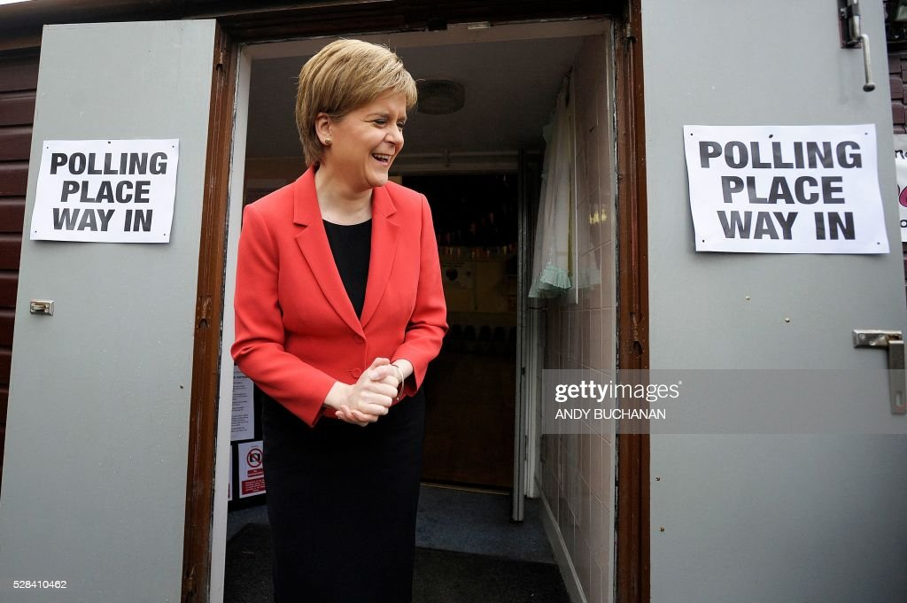 Scotland's First Minister and Leader of the Scottish National Party (SNP), Nicola Sturgeon, poses for photgraphers as she leaves a Polling Station at Broomhouse Community Hall in east Glasgow, on May 5, 2016, after casting her ballot paper to vote. With London choosing a new mayor today, there are also elections to the Scottish, Welsh and Northern Irish assemblies, and 124 local authorities scattered across England. / AFP / Andy Buchanan