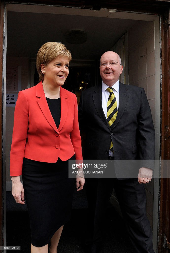 Scotland's First Minister and Leader of the Scottish National Party (SNP), Nicola Sturgeon (L), and her husband Peter Murrell pose for photgraphers as they leave a Polling Station at Broomhouse Community Hall in east Glasgow, on May 5, 2016, after casting their ballot papers to vote. With London choosing a new mayor today, there are also elections to the Scottish, Welsh and Northern Irish assemblies, and 124 local authorities scattered across England. / AFP / Andy Buchanan