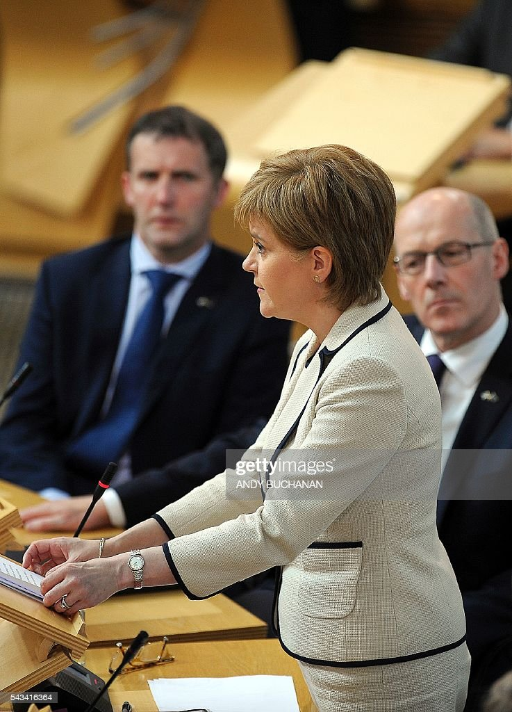 Scotland's First Minister and Leader of the Scottish National Party (SNP), Nicola Sturgeon addresses the Scottish Parliament in a debate on the EU Referendum result and the implications for Scotland, in Edinburgh, Scotland on June 28, 2016. Scottish First Minister Nicola Sturgeon said she would travel to Brussels on Wednesday for talks to defend Scotland's place in the European Union after a vote by Britain as a whole to leave the bloc. Sturgeon said she was 'utterly determined' to protect Scotland as she asked an emergency session of the Scottish parliament on Tuesday for a formal mandate for direct talks with the European Union institutions. / AFP / Andy Buchanan