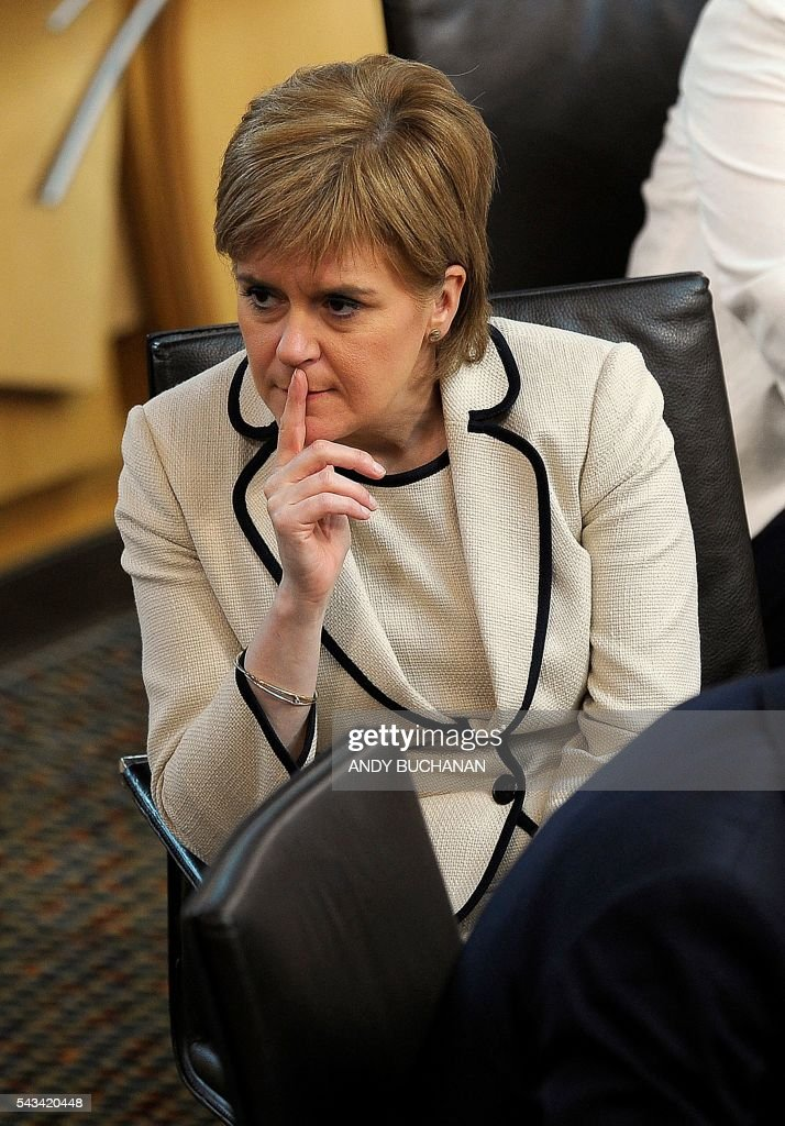 Scotland's First Minister and Leader of the Scottish National Party (SNP), Nicola Sturgeon (R) gestures during a break in the debate on the EU Referendum result and the implications for Scotland at the Scottish Parliament in Edinburgh, Scotland on June 28, 2016. Scottish First Minister Nicola Sturgeon said she would travel to Brussels on Wednesday for talks to defend Scotland's place in the European Union after a vote by Britain as a whole to leave the bloc. Sturgeon said she was 'utterly determined' to protect Scotland as she asked an emergency session of the Scottish parliament on Tuesday for a formal mandate for direct talks with the European Union institutions. / AFP / Andy Buchanan