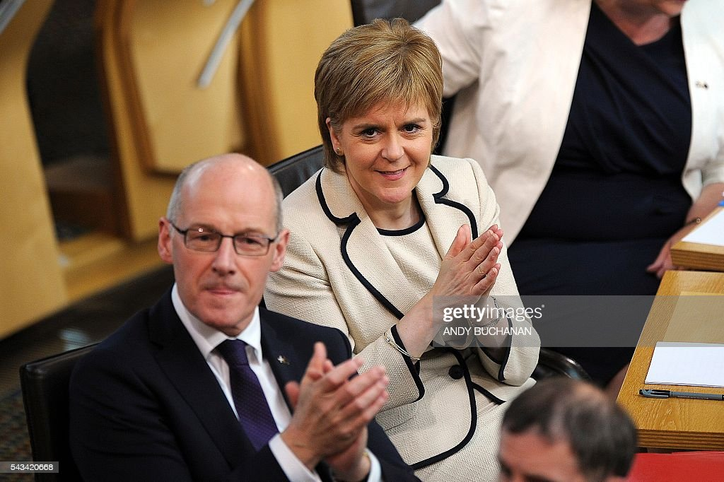 Scotland's First Minister and Leader of the Scottish National Party (SNP), Nicola Sturgeon (R) applauds during a debate on the EU Referendum result and the implications for Scotland at the Scottish Parliament in Edinburgh, Scotland on June 28, 2016. Scottish First Minister Nicola Sturgeon said she would travel to Brussels on Wednesday for talks to defend Scotland's place in the European Union after a vote by Britain as a whole to leave the bloc. Sturgeon said she was 'utterly determined' to protect Scotland as she asked an emergency session of the Scottish parliament on Tuesday for a formal mandate for direct talks with the European Union institutions. / AFP / Andy Buchanan
