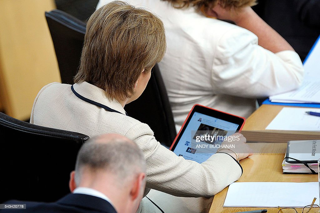 Scotland's First Minister and Leader of the Scottish National Party (SNP), Nicola Sturgeon (R) checks her Twitter feed during a break in the debate on the EU Referendum result and the implications for Scotland at the Scottish Parliament in Edinburgh, Scotland on June 28, 2016. Scottish First Minister Nicola Sturgeon said she would travel to Brussels on Wednesday for talks to defend Scotland's place in the European Union after a vote by Britain as a whole to leave the bloc. Sturgeon said she was 'utterly determined' to protect Scotland as she asked an emergency session of the Scottish parliament on Tuesday for a formal mandate for direct talks with the European Union institutions. / AFP / Andy Buchanan