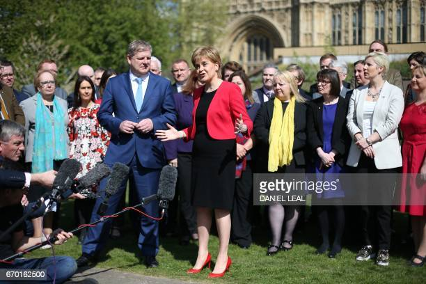 Scotland's First Minister and Scottish National Party leader Nicola Sturgeon talks next to deputy leader and Westminster MP Angus Robertson in front...