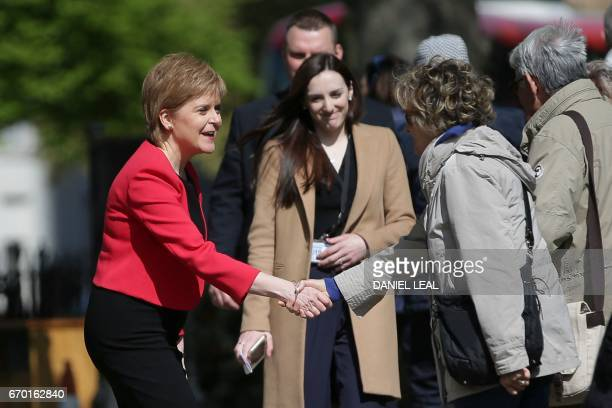Scotland's First Minister and Scottish National Party leader Nicola Sturgeon shakes hands with a member of the public during a media facility outside...