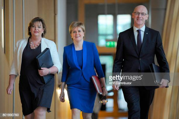 Scotland's First Minister and Scottish National Party leader Nicola Sturgeon walks to the chamber with Deputy First Minister John Swinney and Fiona...