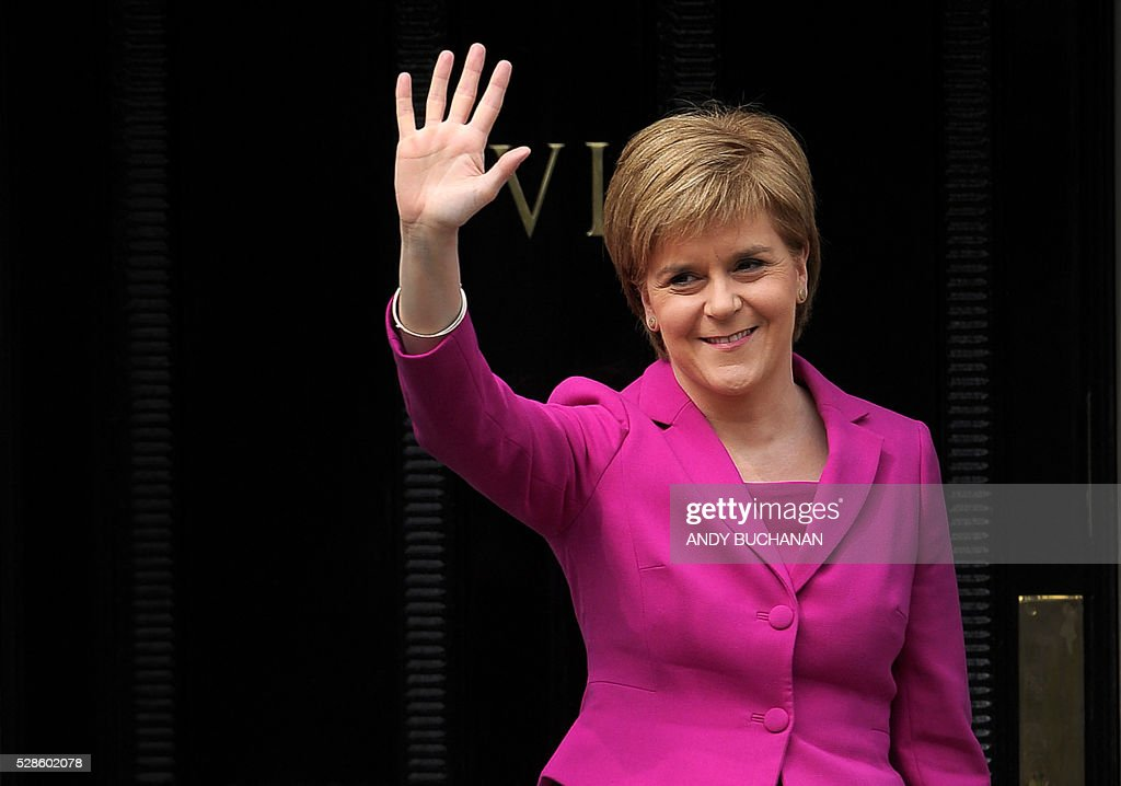 Scotland's First Minister and SNP leader Nicola Sturgeon waves to the media in Edinburgh, Scotland, on May 6, 2016. Scottish nationalists won a third term in power but lost their outright majority Friday in one of a series of local and regional elections seen as a key test for Labour leader Jeremy Corbyn. / AFP / Andy Buchanan
