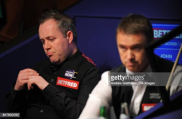Scotland's John Higgins looks dejected as he waits for the tabs to reset alongside his opponant Stephen Hendry during the Betfredcom World Snooker...