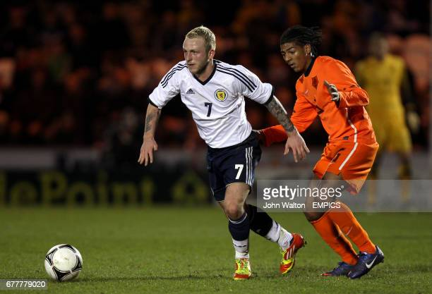 Scotland's Johnathon Russell gets away from the challenge of Netherlands' Patrick Van Aanholt