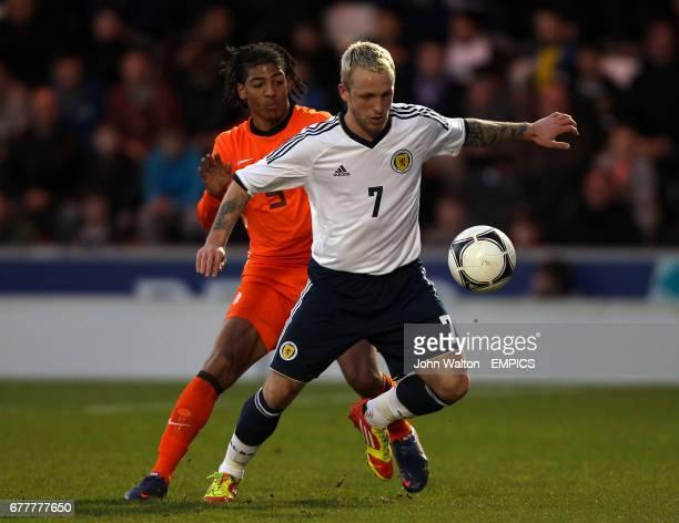 Scotland's Jonhnathon Russell holds off the challenge of Netherlands' Patrick Van Aanholt