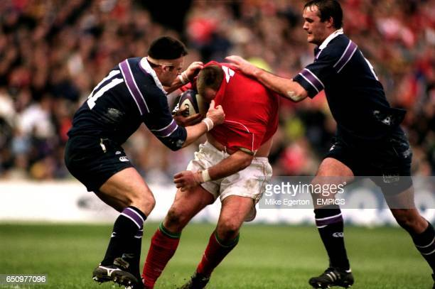 Scotland's Kenny Logan tries to pull the shirt off the back of Wales' Scott Quinnell helped by teammate Martin Leslie