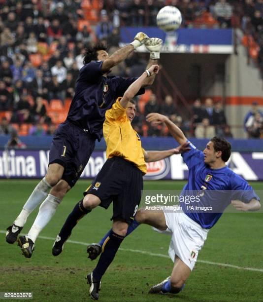Scotland's Kenny Miller challenges Italy's goalkeeper Gianluigi Buffon and Giorgio Chiellini