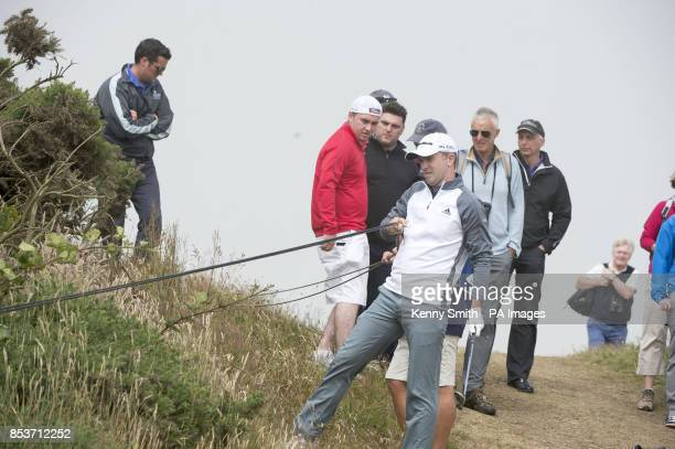 Scotland's Marc Warren has to move TV cables in order to play his shot from the deep rough during day three of the Aberdeen Asset Management Scottish...